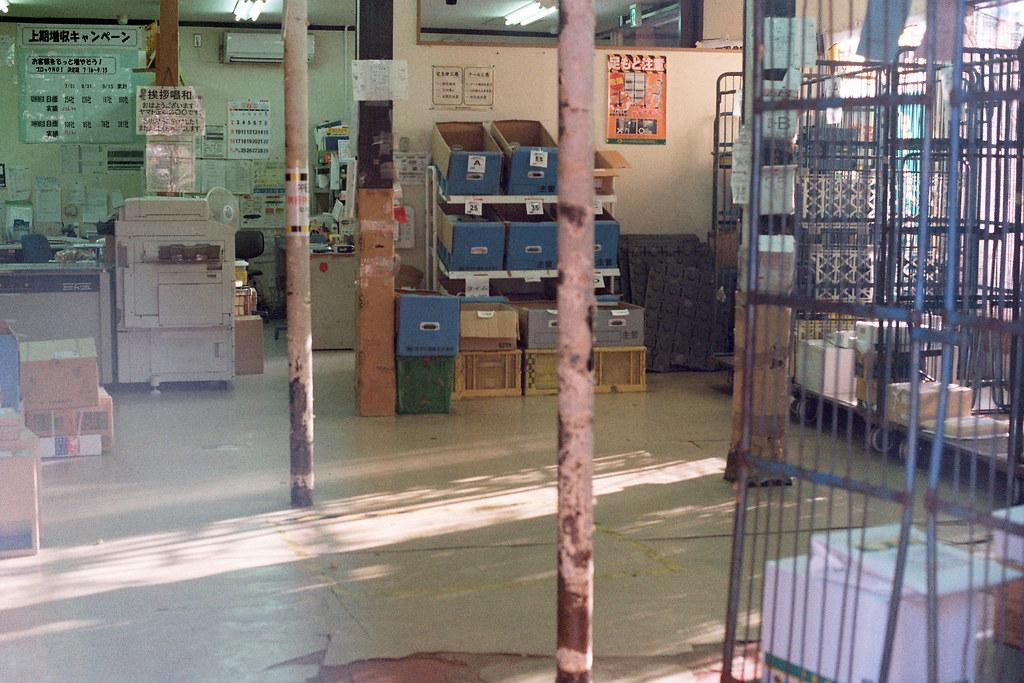 """黑貓宅急便 千葉市(ちばし) 2015/08/05 從千葉城走下來的路口看到黑貓宅急便的營業處,那時候黃昏,我就對著店裡拍照,一直很擔心會有人出來制止,但發現好像沒有人在,等我拍完之後走過一個轉角,發現原來店員正在販賣機前面思考要喝什麼 ...  Nikon FM2 / 50mm Kodak ColorPlus ISO200  <a href=""""http://blog.toomore.net/2015/08/blog-post.html"""" rel=""""noreferrer nofollow"""">blog.toomore.net/2015/08/blog-post.html</a> Photo by Toomore"""