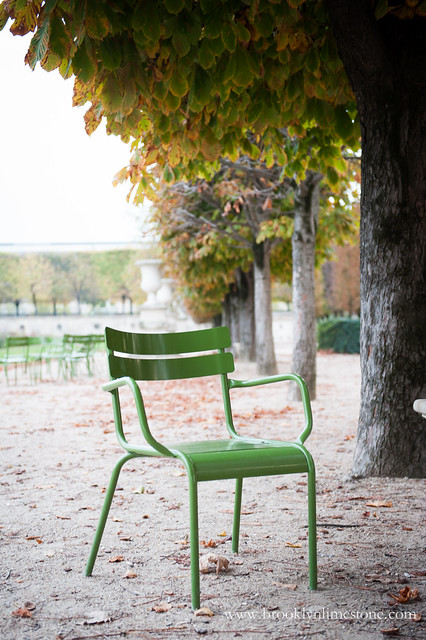 A bright green metal chair sitting alone in a Paris Park