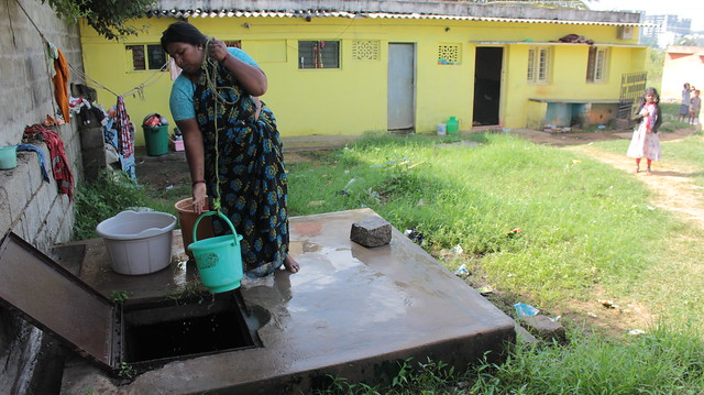 A wealthier resident draws water from a well on her property. The well water is charged by the lake.