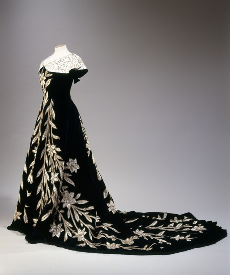 """Lily Dress"" evening dress, black velvet with application of ivory silk in the form of lilies, embroidered with pearls and sequins, 1896. © L. Degrâces et Ph. offre/Galliera/Roger-Viollet"