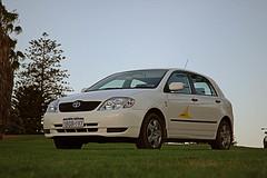sedan(0.0), automobile(1.0), automotive exterior(1.0), toyota(1.0), wheel(1.0), vehicle(1.0), toyota corolla e120(1.0), compact car(1.0), bumper(1.0), land vehicle(1.0),