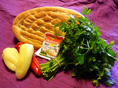 A flat, oval loaf of bread, lying on a purple tablecloth.  In front of the bread are a large bunch of flat-leaf parsley, a packet of Bulgarian goat milk cheese, and three long bell peppers, one red and two white.