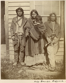 Metis: two men, one woman, one child, posed in front of a building at Dufferin, Manitoba / Deux hommes, une femme et un enfant métis, Fort Dufferin (Manitoba)