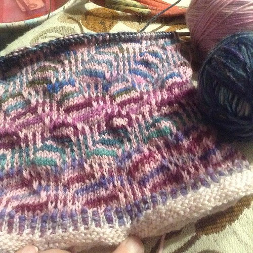 36 of 65 pattern rows and some weaving in of ends inside done. On 3rd mini of semi-solid pink and 4th of variegateds. Getting into darker blues & greens in variegated yarn ball. #foulcowl