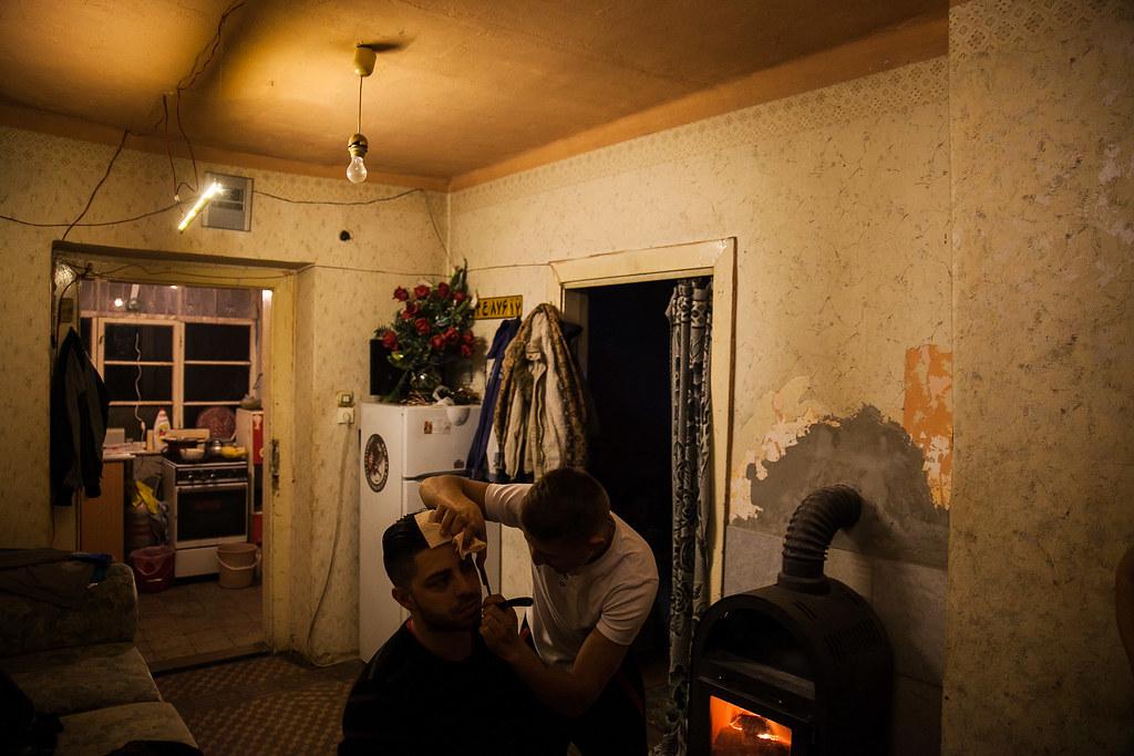 A nappaliban, ahová telefon-töltőt is szereltek a rendszerre Károly fodrász-tanonc fia borotválja egy barátjukat, a hátsó szobában pedig másik fia mutatja a LED-sor fényét | Fotók: Magócsi Márton