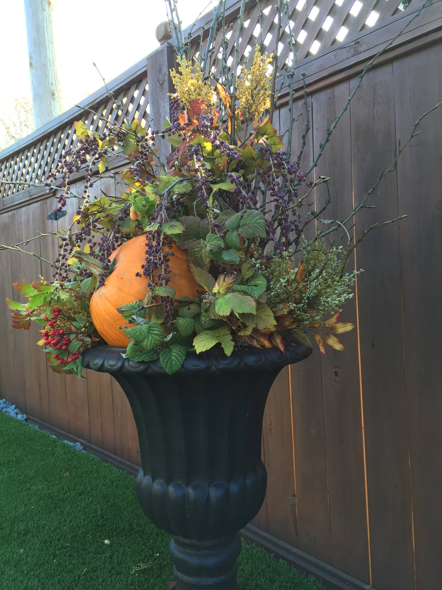 black outdoor urn filled with harvest arrangement and pumpkin