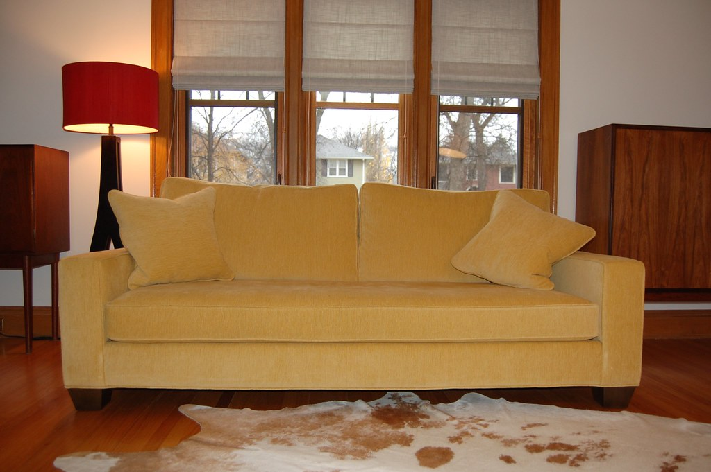 classic sofa in yellow fabric in front of wood windows