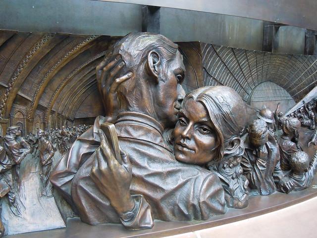 Une jeune femme phubbant son ami, frise sous la sculpture The Meeting Place de Paul Day à la Gare de Saint-Pancras1.