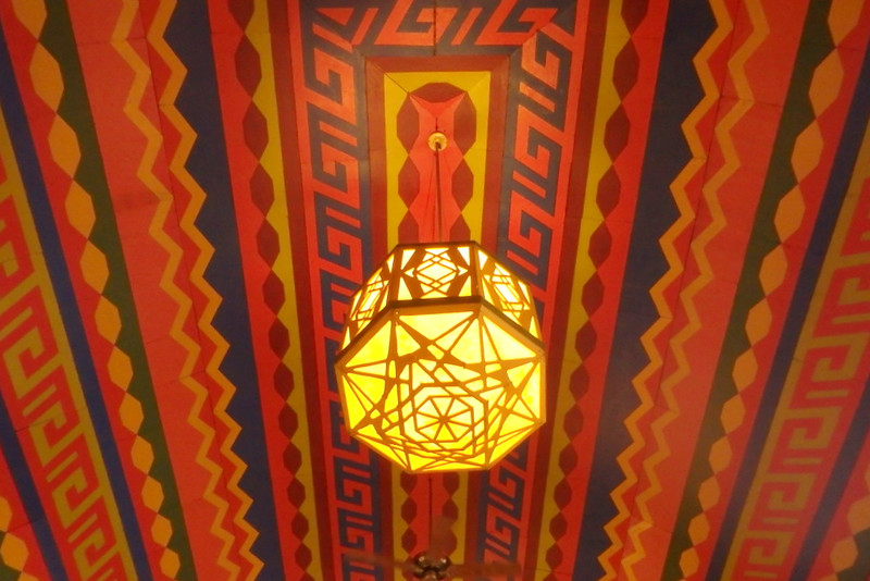 a hanging light fixture underneath a multicolor, patterned ceiling