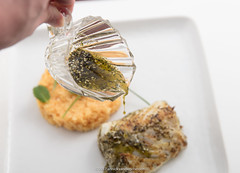 Pouring za'atar-wu-zayt sauce on codfish dish…