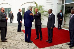 With Haitian Prime Minister Evans Paul looking on, U.S. Secretary of State John Kerry is greeted by Haitian President Michel Martelly before their bilateral meeting at the Presidential Palace in Port-au-Prince, Haiti, on October 6, 2015. [State Department photo/ Public Domain]