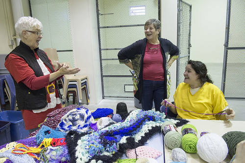 Volunteers Susan Smalley and Twyla Mundy share a laugh with Lisa Mann during a visit to help Mann and other female inmates at Wildwood Pretrial Facility who participate in a prison knitting program. The colorful products of the women's work go to benefit
