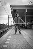 Man ironing his suit in the city on the platform of a train station by CloudMineAmsterdam