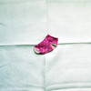Little pink sock adrift in the creases and folds of negative space