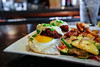 Colonel Egg Benedict - Two Fried Eggs/Buttermilk Biscuit/Fried Chicken Fritters/ Honey Baked Ham/Jalapeno Gravy - Iron Horse Tavern