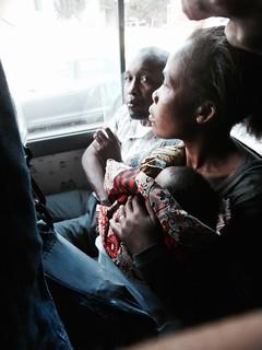 Maputossa mies, nainen ja capulana-kankaaseen kiedottu vauva chapa-minibussin kyydissä.