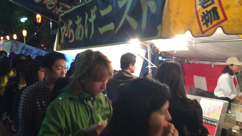 Walking on the sidewalk next to street food vendors in Shinjuku.