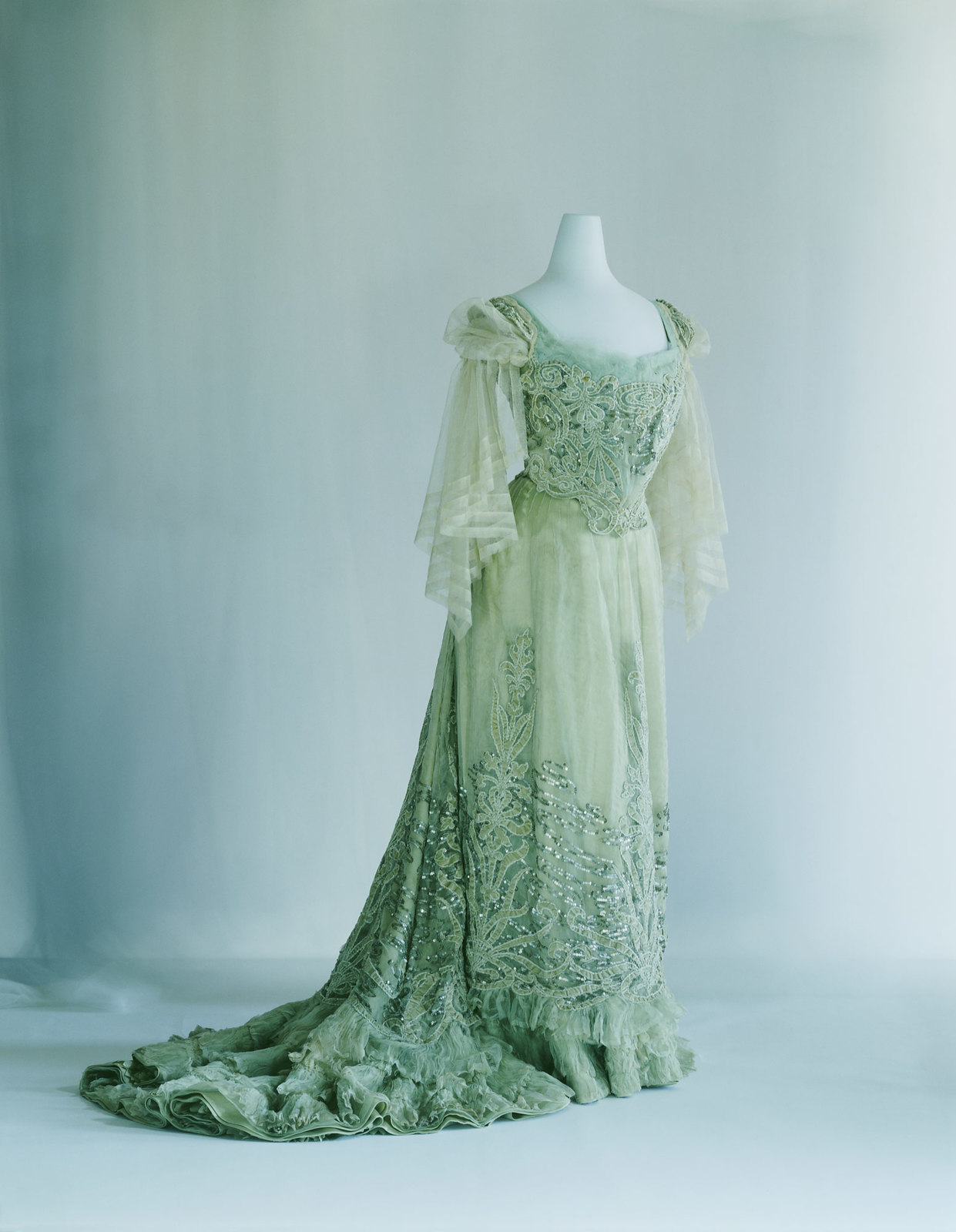1900. Evening Dress. Pale green silk chiffon and velvet; S-curve silhouette; appliqué of plant pattern; sequin and cord embroidery with water's-edge pattern. Credit KCI