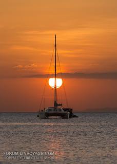 Sunset with sun at sail catamaran, Koh Phayam island, southern Thailand      XOKA0766BIIs