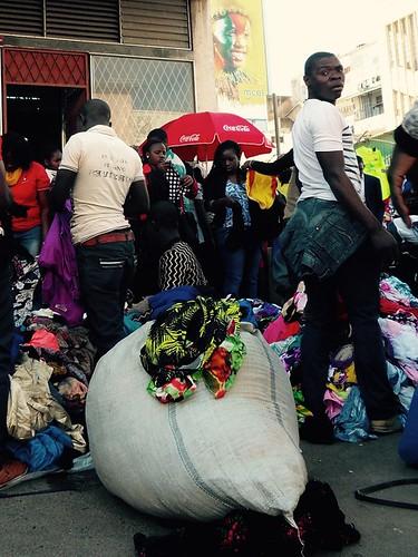Maputossa ihmiset ostavat katumyyjiltä uusia ja luultavasti länsimaisia käytettyjä vaatteita. Taustalla nauraa valtavan Mcel-liittymämainoksen tyttö.