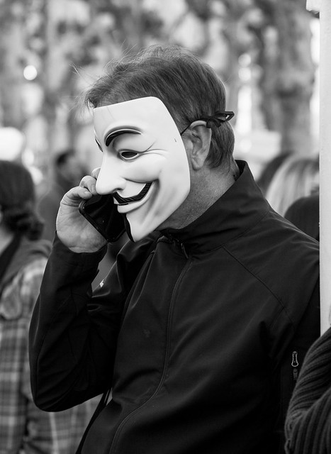 Guy Fawkes on the phone at NoBanNoWallSF Rally - Feb 4, 2017