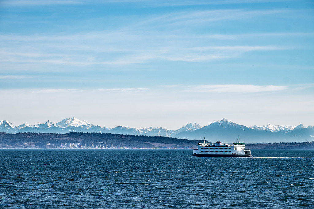 Washington State Ferry traveling between Port Townsend and Coupville on Whidbey Island. Cascade Mountains in the backdrop.