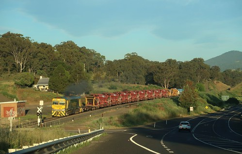 Heading towards the early morning sun, GL112 brings ballast cleaning track maintenance train 5M52 through Blandford, NSW