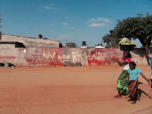 """Zavalassa nainen ja lapsi capulana-hameissaan kävelevät kylän punaruskeahiekkaisella tiellä ja taustan muuriin on tehty syrjimisenvastainen teos """"HIV:llä ei ole ikää."""""""