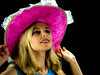 Pretty woman in blue dress holding pink hat
