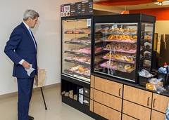 U.S. Secretary of State John Kerry considers his options as he prepares to buy doughnuts at the newly opened Massachusetts-based Dunkin' Donuts franchise in the State Department cafeteria in Washington, D.C., on September 4, 2015. [State Department photo/ Public Domain]