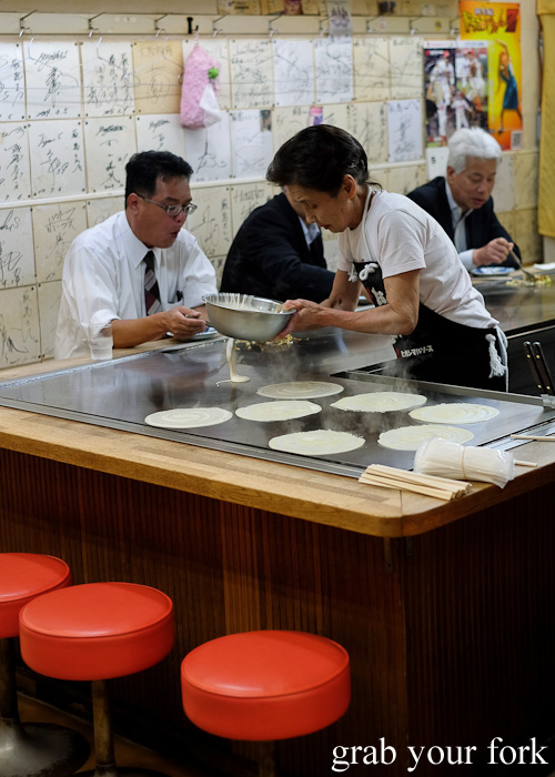 Customers eating at an okonomiyaki counter at Okonomimura, Hiroshima