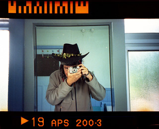 reflected self-portrait with Pentax efina T camera and bi-seasonal hat