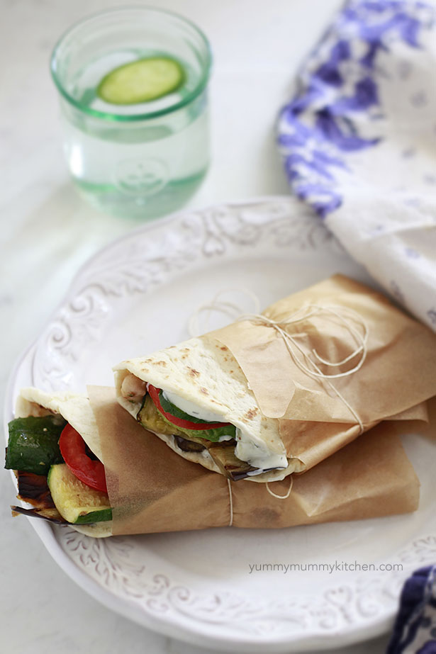 Vegetarian gyros filled with vegetables and tzatziki and wrapped with parchment paper.