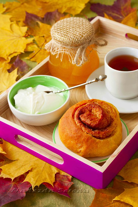 cup of tea, honey, yogurt and pumpkin muffin on a tray on background of autumn leaves