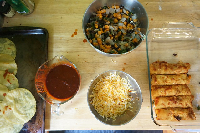 Work station for assembling enchiladas: a baking sheet of fried tortillas, a cup of sauce, a bowl of shredded cheese, another of filling, and a baking dish half-filled with rolls of cheesy vegetable goodness.