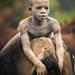 Young Suri Boy Sitting on a Cow by John Rowe Photo