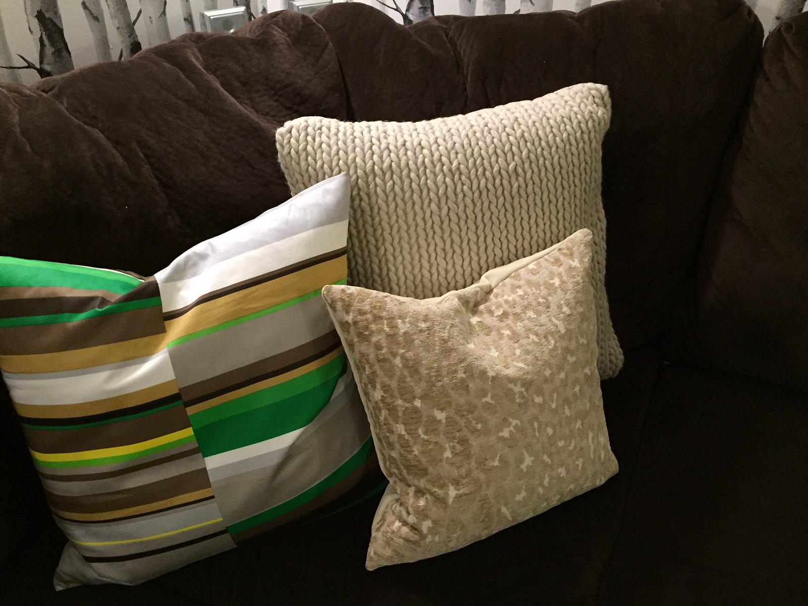 selection of cushions on brown sofa