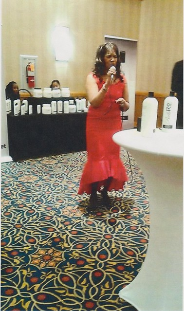 Barbara Pollard sining with a microphone wearing a red dress
