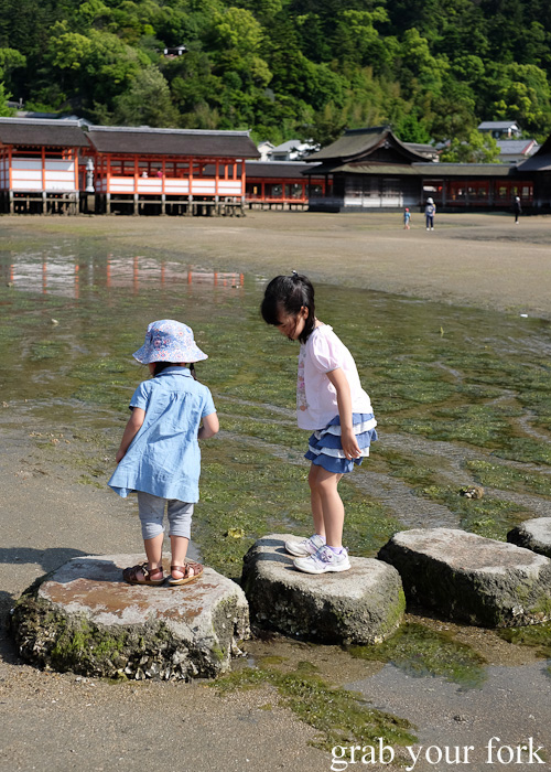 Local kids playing on stepping stones in front of the Itsukushima Shrine on Miyajima Island
