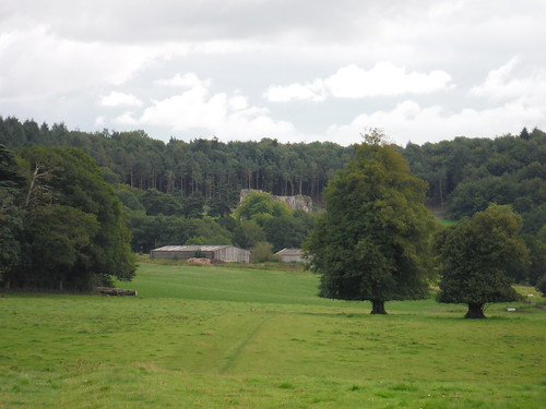 Old Wardour Castle beyond farm buildings, in front of The Hanging (wood)