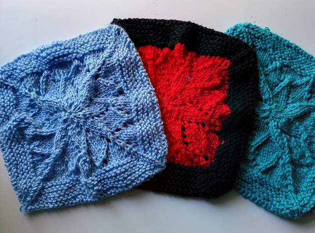 Three blanket squares laid out: blue, red with a black border, and aqua