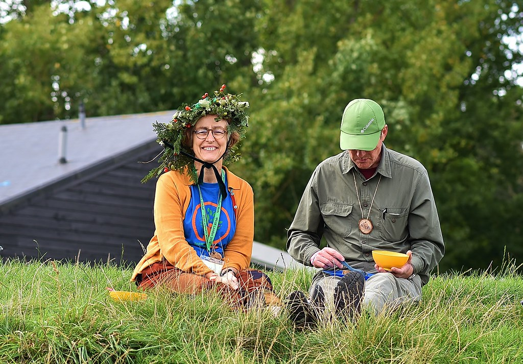 Helen wearing a hat in a field alongside a man eating lunch