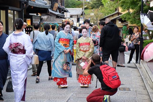 Two women dressed as geishas get their photo taken