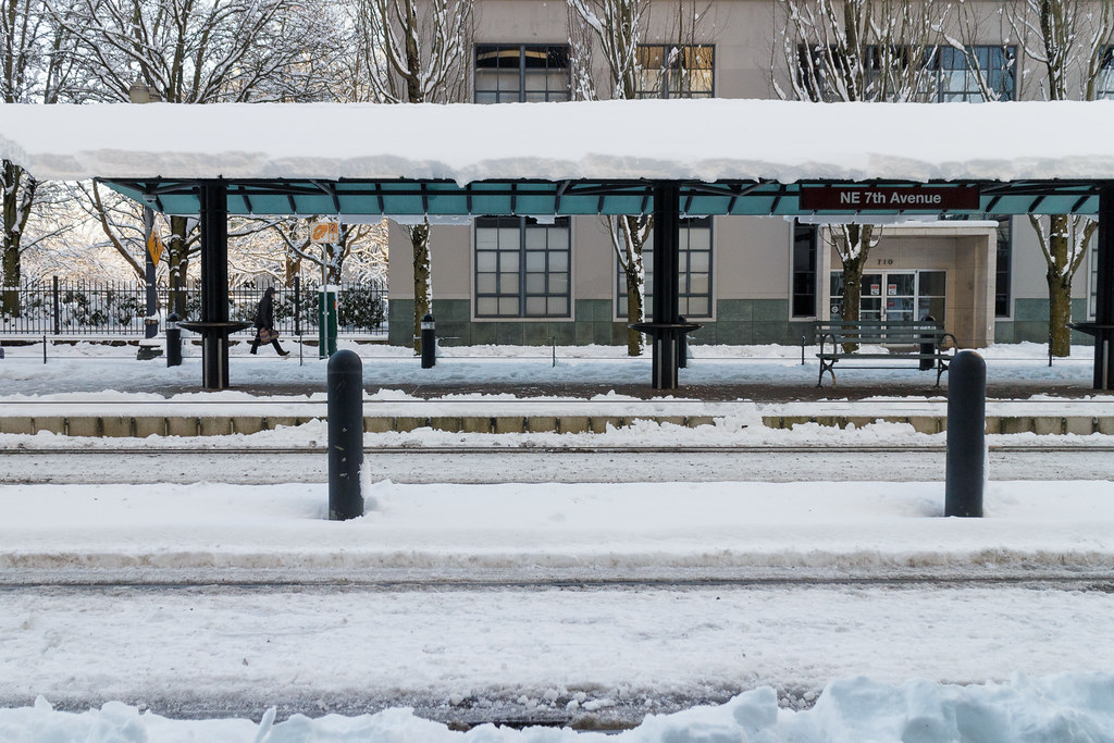 Snow surrounds the train tracks at the NE 7th Avenue MAX station in Portland, Oregon
