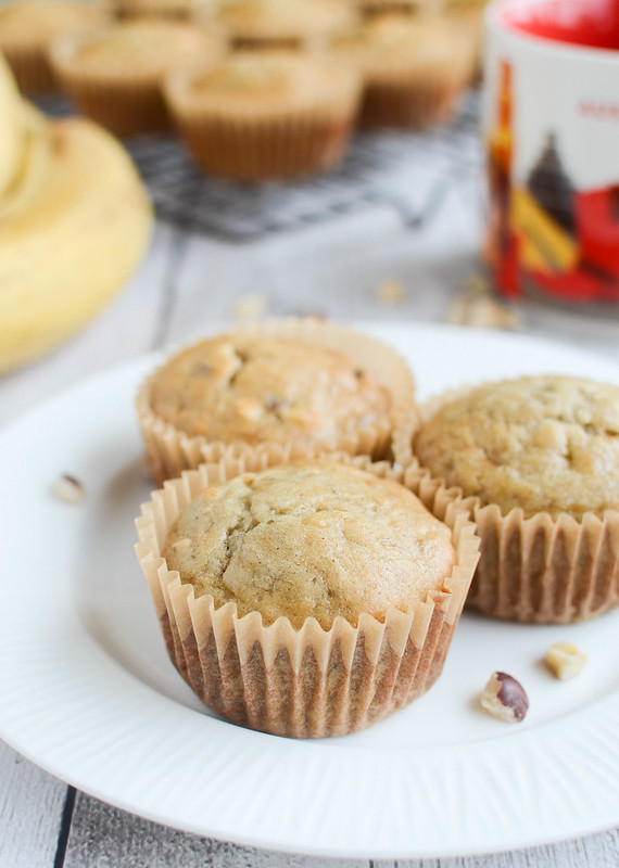 3 banana nut muffins on a white plate; coffee mug, bunch of bananas, and more muffins on a cooling rack in the background