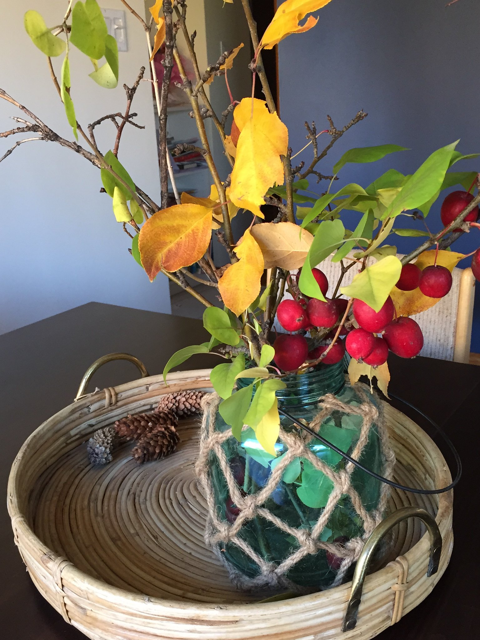 Autumn arrangement in round wicker tray on dining room table