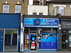 "A small shop in the middle of a terrace, with a blue sign above reading ""E Shop General Store"" and carrying an advert, also blue, for Talk Home Mobile.  The frontage is fully glazed, but mostly covered up by a large blue Talk Home decal and multiple small adverts for things including stamps, Pay Point bill payments, the National Lottery, Oyster, and so on."