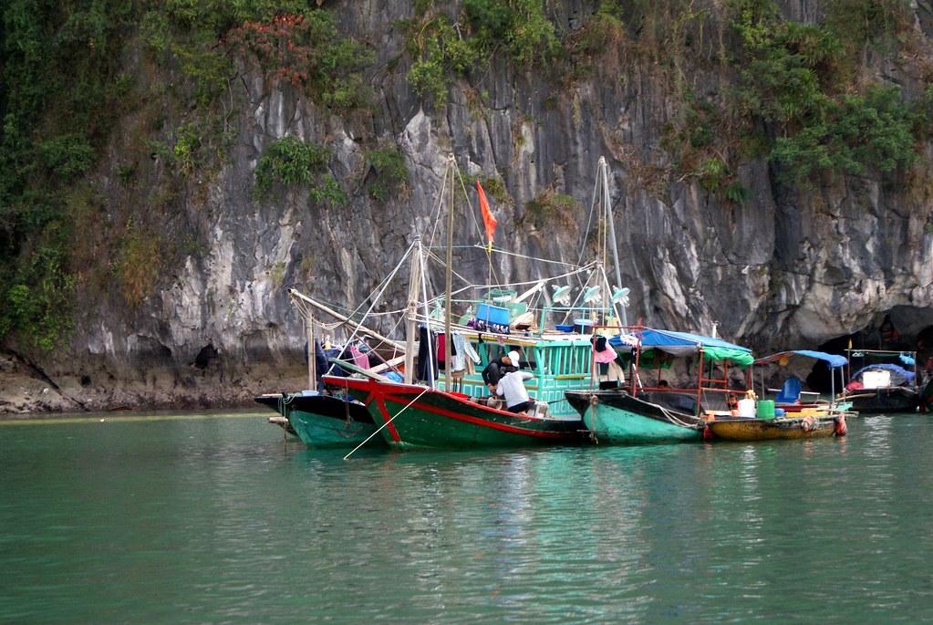 Pêcheurs et barque-épicerie dans la baie d'Halong au Vietnam.