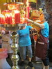 Placing a candle offering, Longshan Temple, Taipei, 2015