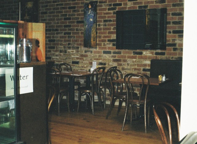 Olinda Cafe. Exposed brick wall, tables and chairs